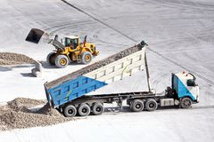Cargo terminal for loading of gypsum cargo by ship cranes to bulk carrier. Port of Salalah, Oman. Cargo terminal for loading of gypsum cargo to bulk carrier by royalty free stock photography