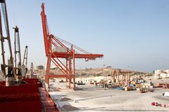 Cargo terminal for loading of gypsum cargo by ship cranes to bulk carrier. Port of Salalah, Oman. Cargo terminal for loading of gypsum cargo to bulk carrier by royalty free stock photo