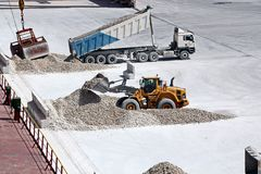 Cargo terminal for loading of gypsum cargo by ship cranes to bulk carrier. Port of Salalah, Oman. Cargo terminal for loading of gypsum cargo to bulk carrier by stock photos