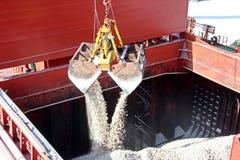 Cargo terminal for loading of gypsum cargo by ship cranes to bulk carrier. Port of Salalah, Oman. stock photo