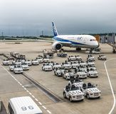 August 18, 2017: Narita International Airport, Tokyo, Japan- Cargo-freight tractors and All Nippon Airlines jetliner stock photography