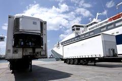 Cargo trailers near docked ship Stock Photos