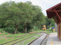 CARGO TRAIN ARRIVING THE SMALL RAILWAY STATION. Freight train, with lights on, in sunny day, arriving at the small empty railway station, in the countryside of Stock Photography