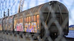 Cargo train behind fence. Royalty Free Stock Photos
