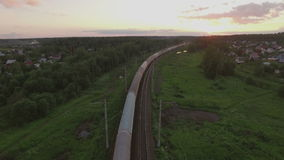 Cargo train crossing countryside at sunset, Russia. Aerial shot of cargo train running through the village in the woods at sunset, Russia stock video footage