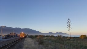 Cargo train departing from train station during twilight hours in Kaikoura, New Zealand stock photography
