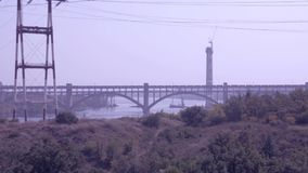 The cargo train moves on the bridge across the river. Trading train moves on the bridge across the river stock video footage
