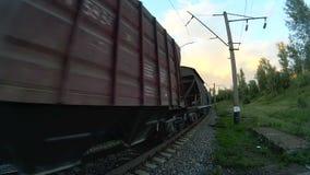Cargo train passing on railroad tracks stock footage