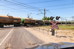 Cargo train riding over a railway crossing Royalty Free Stock Images