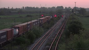 Cargo Train Transportation on Railways, Freight Train Running Towards Station. In Sunset stock footage
