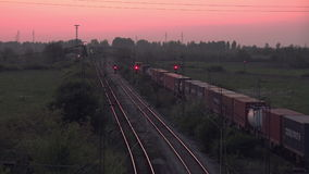 Cargo Train Transportation on Railways, Freight Train Running Towards Station. In Sunset stock video