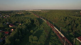Cargo trains moving through the village, aerial view. Aerial - Freight trains making their way through the countryside, Russia stock video
