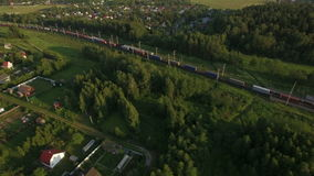 Cargo trains traveling in the countryside, Russia. Aerial view of railway traffic running through the countryside and village, Russia stock footage