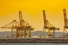 Cargo and transportation industry - cargo shipping and commercial terminal in seaport at sunset. Industrial landscape with gantry stock images