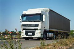 The truck with white cabin carries cargo on the highway in the t. Cargo truck with tilt van transporting goods on highway. Front view. Wide angle. White cabin Royalty Free Stock Images