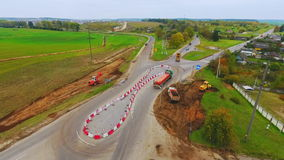 Cargo trucks moving on country road. View from above. suburban road construction. Cargo trucks moving on country road. View from above. Drone view suburban road stock video footage