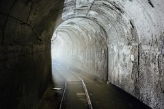 Cargo tunnel in abandoned soviet bunker with railway. Turn the tunnel. Light from the turn. Tunnel in abandoned soviet bunker with railway. Turn the tunnel Stock Photos