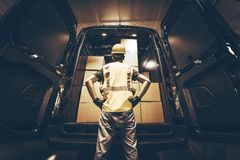 Cargo Van Delivery. Rear Cargo Doors Reloading. Construction Guy Talking Care of Fresh Supplies Delivery. Large Cargo Van with Many Cardboard  Boxes Waiting Stock Images