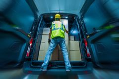 Cargo Van Loading. Large Heavy Duty Cargo Van Loading by Men in Yellow Helmet. Shipping and Logistics Theme Stock Image