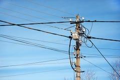 Cargo velho da eletricidade contra o céu azul Fotografia de Stock Royalty Free