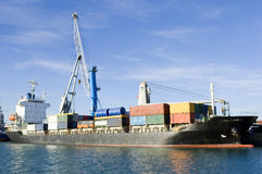Cargo vessel. At port being loaded Stock Photo
