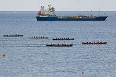 Cargo Vessel and Gig Racers off Falmouth UK Royalty Free Stock Image