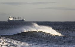 Cargo vessel on the high seas. A cargo ship on the horizon with a wave and sea spray in the foreground Stock Photography