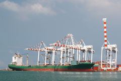 Cargo vessel and large crane operating at the seaport Stock Photos