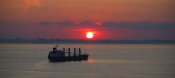 Cargo vessel at sunset Stock Images
