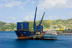 Cargo vessels at a customs wharf in the caribbean. Ships tied to a dock at kingstown port in the grenadines stock photos