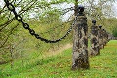 Cargos de pedra velhos com uma cerca do elo de corrente do ferro Imagens de Stock Royalty Free