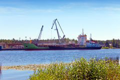 Cargoship unloading on the river Luga. Russia Royalty Free Stock Images