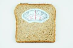Cargue la escala con la rebanada de pan sana en el fondo blanco Imagen de archivo