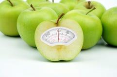 Cargue la escala hecha de manzana verde en el fondo blanco Fotos de archivo