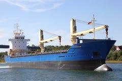 Cargueiro com os guindastes no canal de Kiel foto de stock