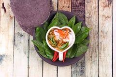 Cari coulé de poissons dans la tasse en forme de coeur Photo stock