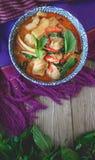 Cari rouge de poulet thaïlandais sur le tissu thaïlandais et le vieux fond en bois Photo libre de droits