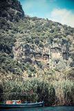 Carian rock tombs. Dalyan river running along the toms with lush vegetation and a boat Royalty Free Stock Images