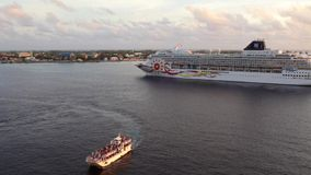 Carib Empress tender boat sailing aside of NCL large cruise ship stock video