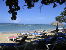 Caribbean beach. With beach chairs at the foreground in shade Stock Images