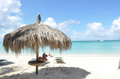 Caribbean beach. Loving couples relax on beautiful beach with umbrella hut Royalty Free Stock Images