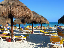 Caribbean beach. With straw umbrellas and yellow chairs stock images
