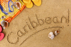 Caribbean beach sand word writing. Beach background with towel and flip flops and the word Caribbean written in sand Stock Images