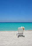 Caribbean beach chair. Empty tropical beach chair with hat at shoreline in the Caribbean stock photos