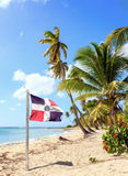 Caribbean beach and Dominican Republic flag. On Saona island Stock Image