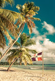 Caribbean beach and Dominican Republic flag Royalty Free Stock Image