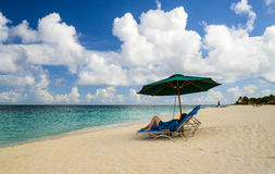 Caribbean Beach Lounger. Female tourist lounges under green umbrella on beatiful beach on Caribbean island of Anguilla Stock Photo