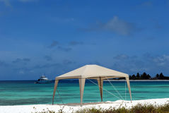 Caribbean beach,tent and yacht  Royalty Free Stock Image