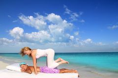 Caribbean beach therapy shiatsu massage on knees. Women in paradise Stock Photos