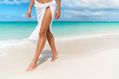 Caribbean beach travel - woman legs closeup walking on sand. Caribbean vacation travel - woman leg closeup walking on white sand relaxing in beach cover-up pareo Stock Image